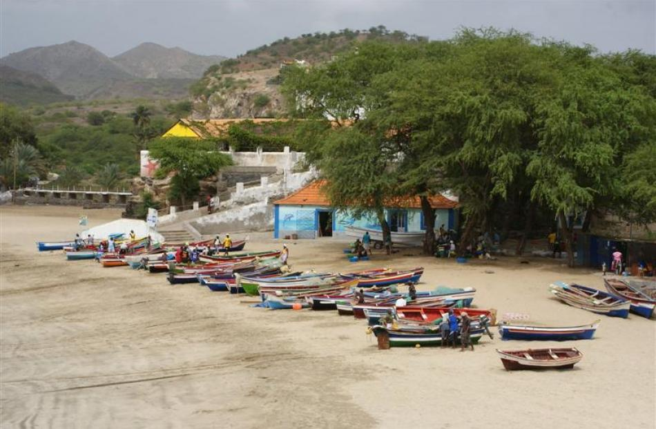 Colourful fishing boats line the white sand.