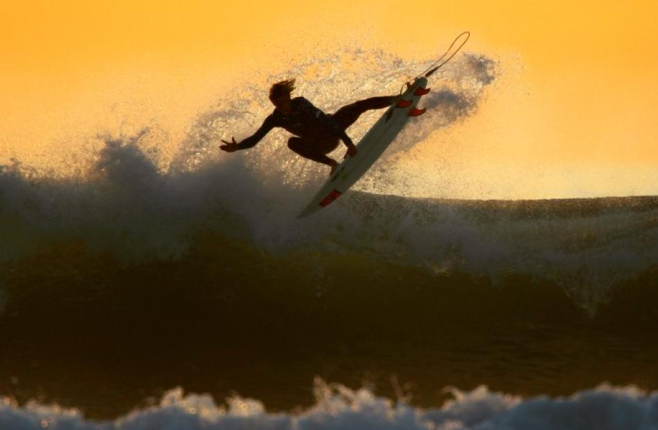 A young surfer sails his board off a wave as large swells hit the California coastline at dusk in...