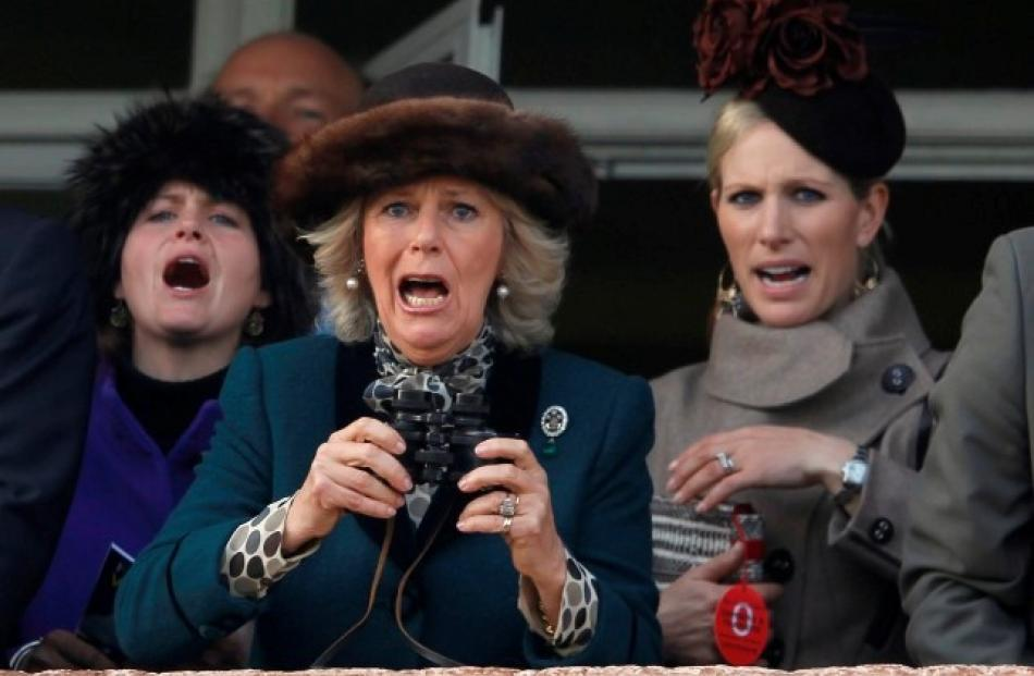 Britain's Camilla, Duchess of Cornwall (C), and Zara Phillips (R) react during The Queen Mother...