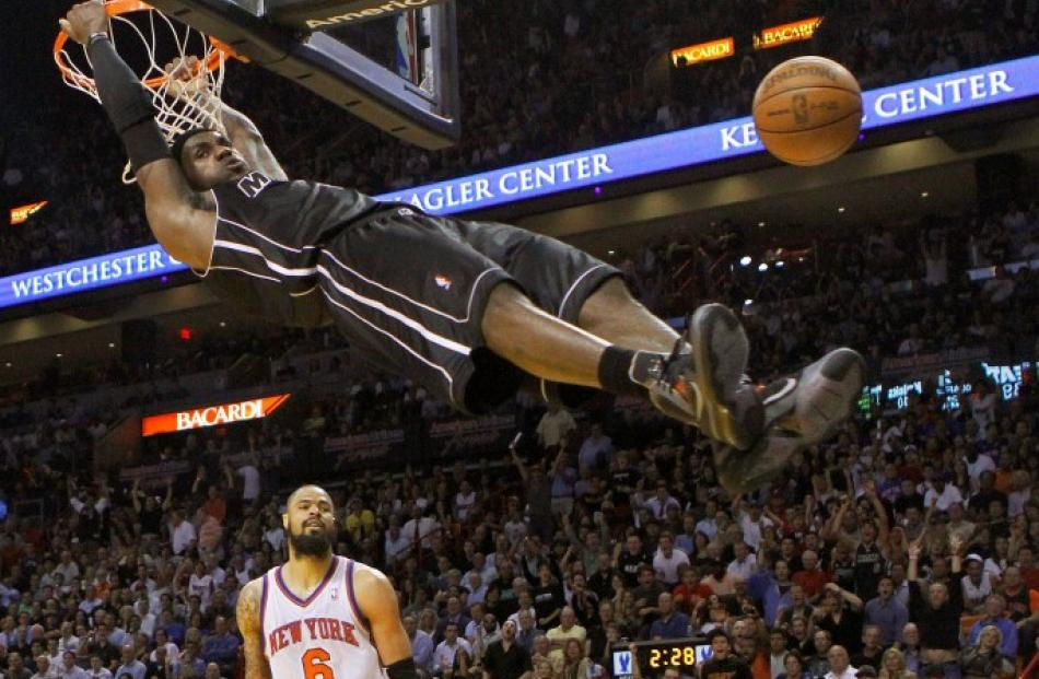 Miami Heat's LeBron James hangs on the rim after his dunk near New York Knicks Tyson Chandler...