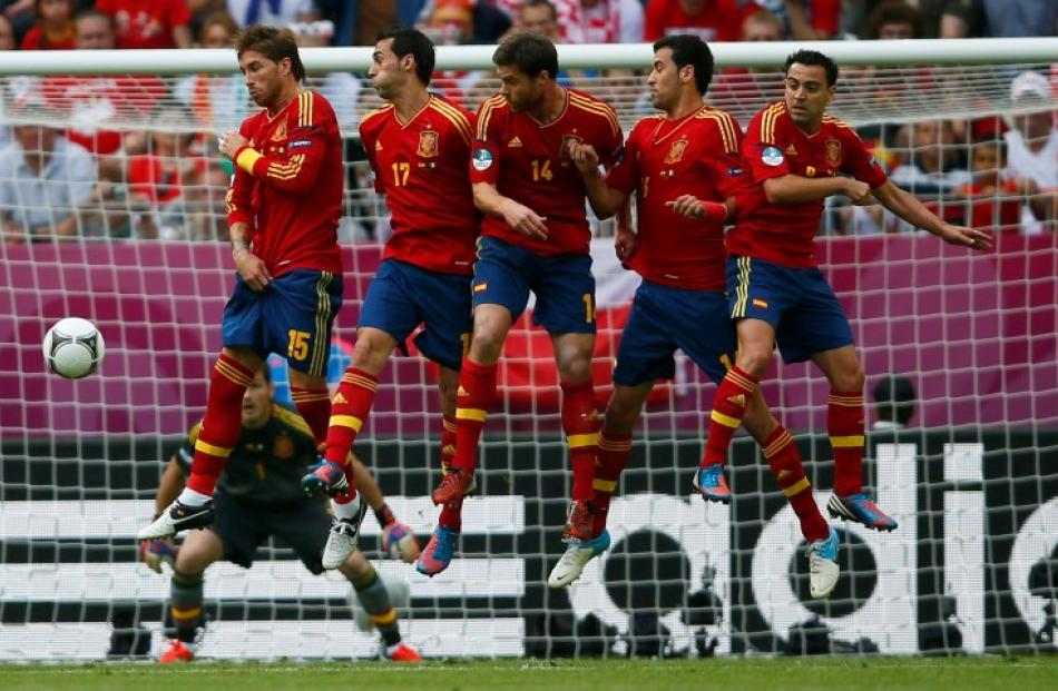 Spain players form a defensive wall as Italy's Andrea Pirlo takes a free kick during their Group...