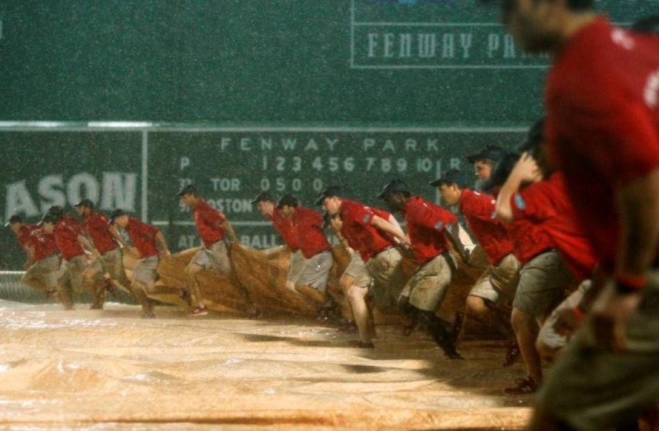 The Fenway Park ground crew covers the field during a rain delay of the MLB American League...