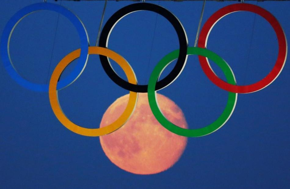The full moon rises through the Olympic Rings hanging beneath Tower Bridge during the London...