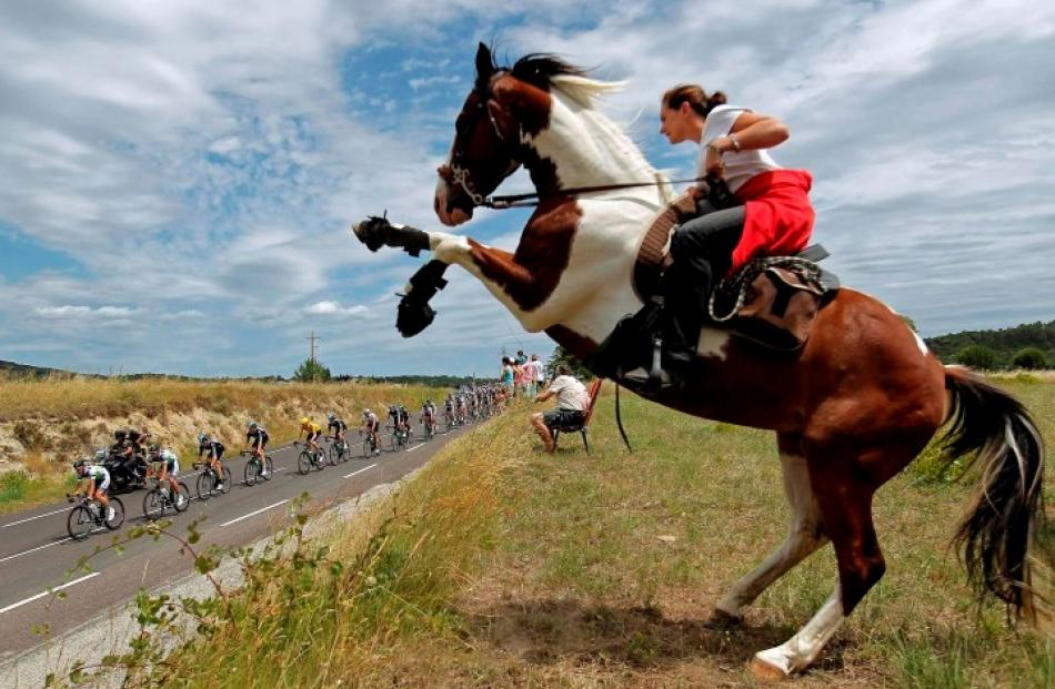 The pack of riders cycles past a woman on a horse during the 13th stage of the 99th Tour de...