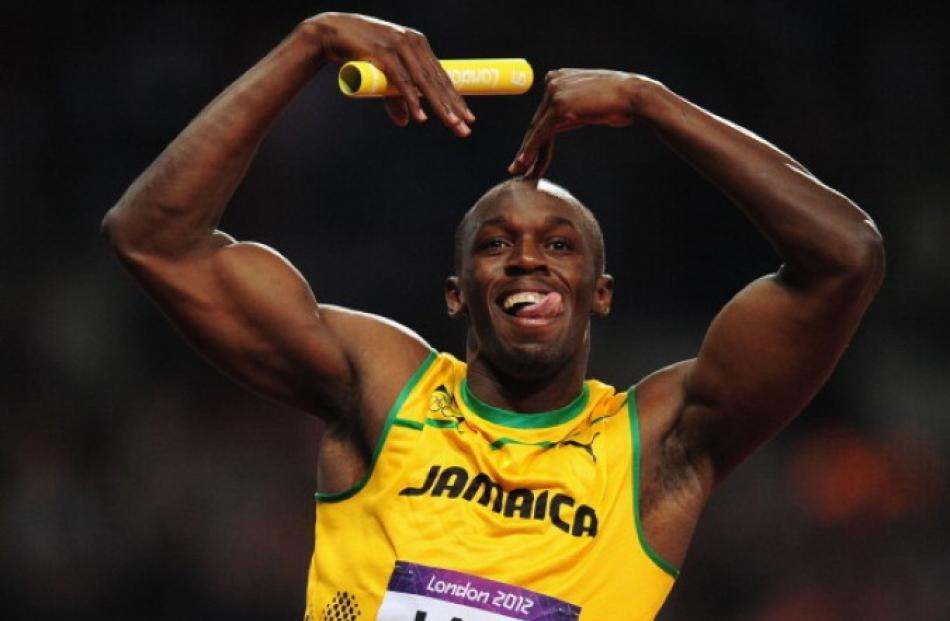 Usain Bolt of Jamaica celebrates winning gold and setting a world record in the men's 4x100m...
