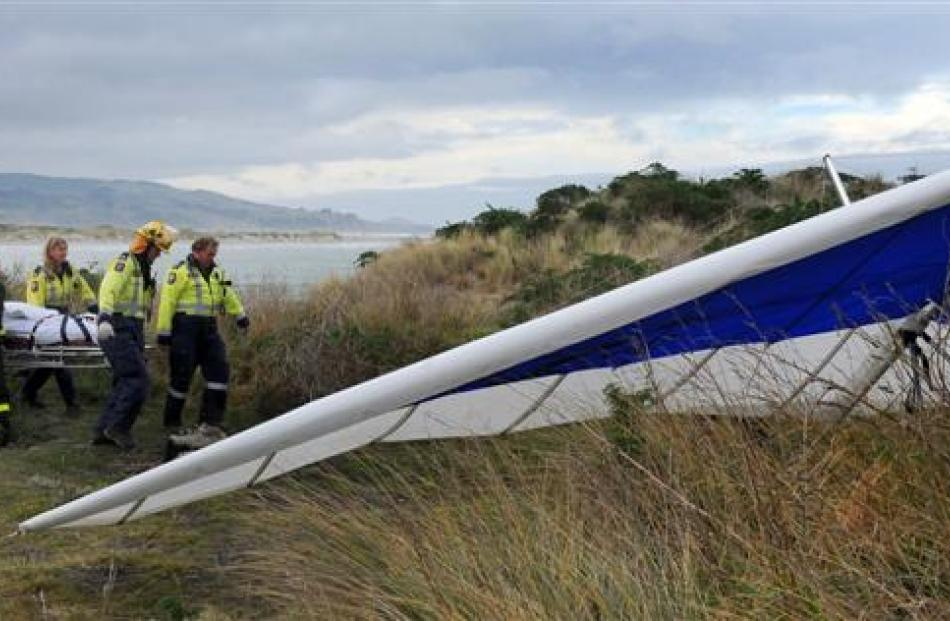 A hang glider pilot is carried by emergency services past a companion's glider, after a crash...