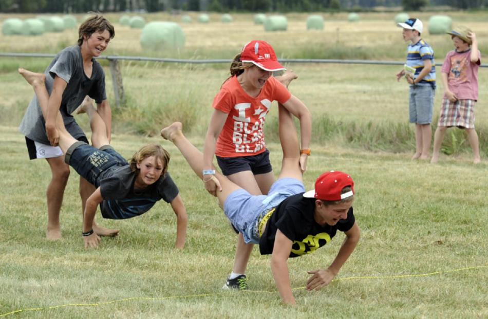 Emma McLeay (12) of Invercargill and Luke Holden (14) of Cromwell cross the finish line to win...