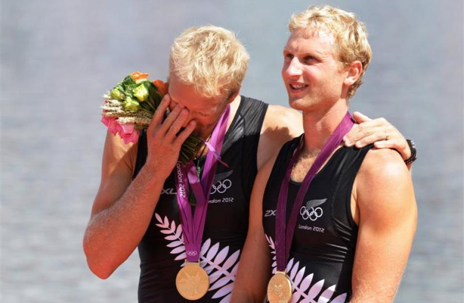 Hamish Bond (right) and his rowing partner, Eric Murray, stand on the podium after winning gold...