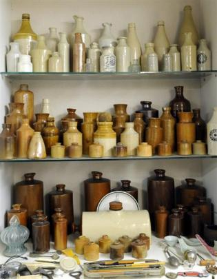 Clay whisky bottles, inkwells, drink containers and other assorted items form a family.