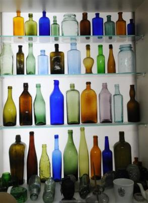 Various glass bottles are backlit in Peter Marsh's display of vintage articles.
