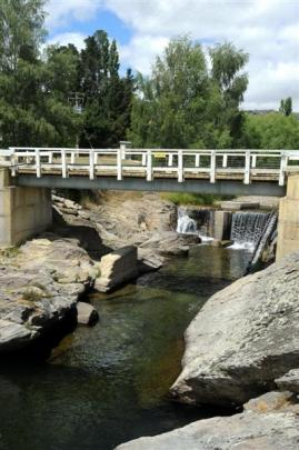 A bridge crosses the Sowburn River next to a swimming hole.