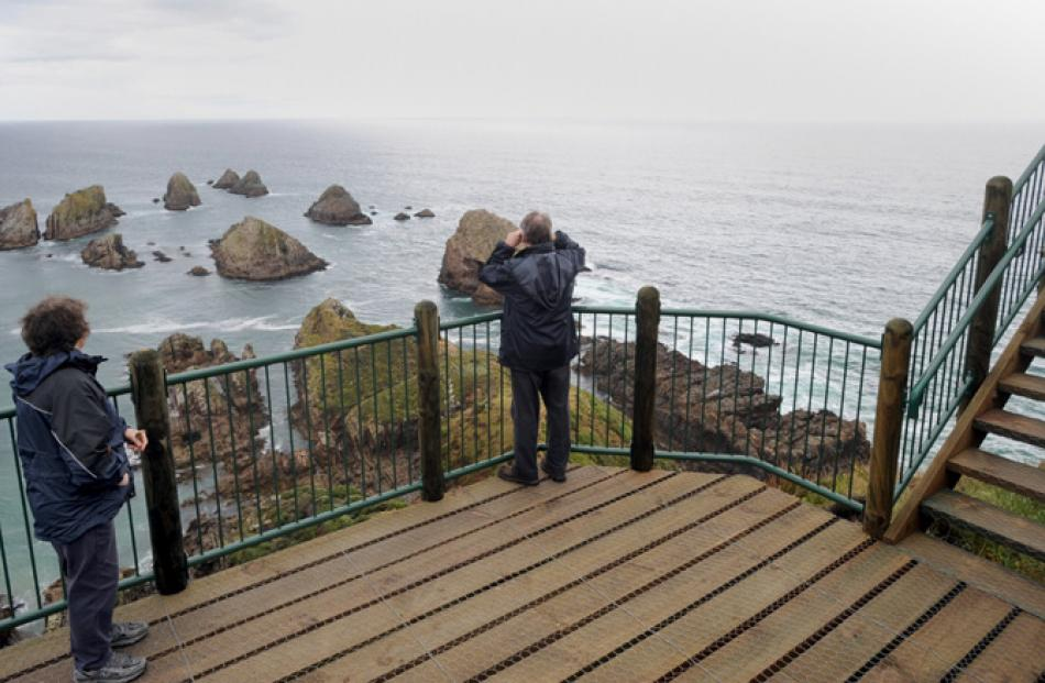 Visitors view  the Nuggets from the Nugget Point lighthouse viewing  platform.