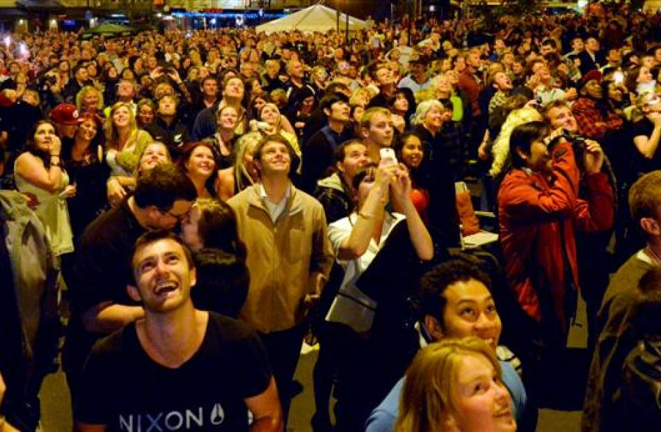 The crowd in the Octagon looks up as fireworks brighten the night sky to welcome 2013 in Dunedin.