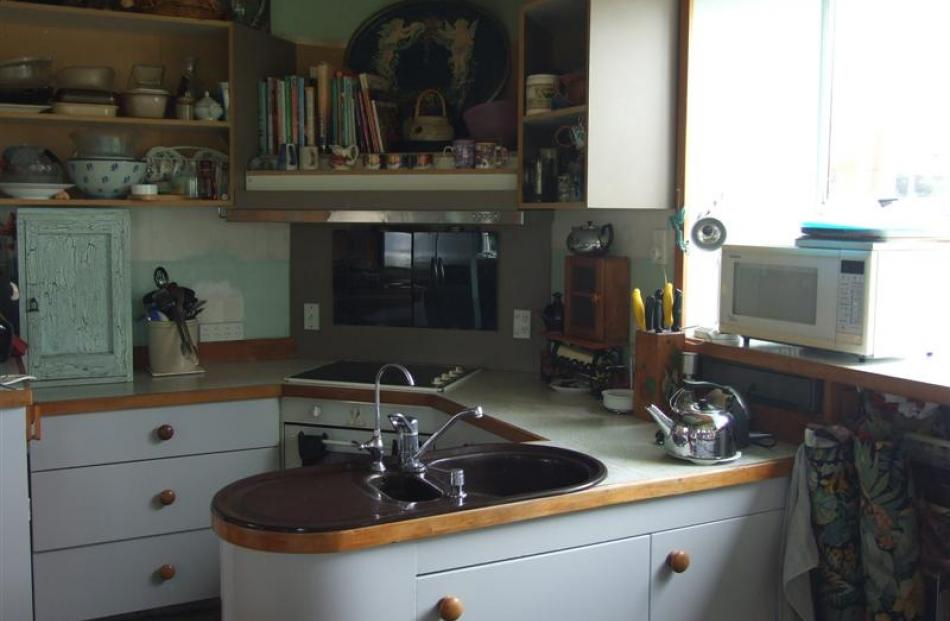 A small kitchen is tucked away, looking towards the backyard.