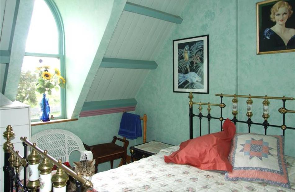 The arched window bathes this guest bedroom in light.