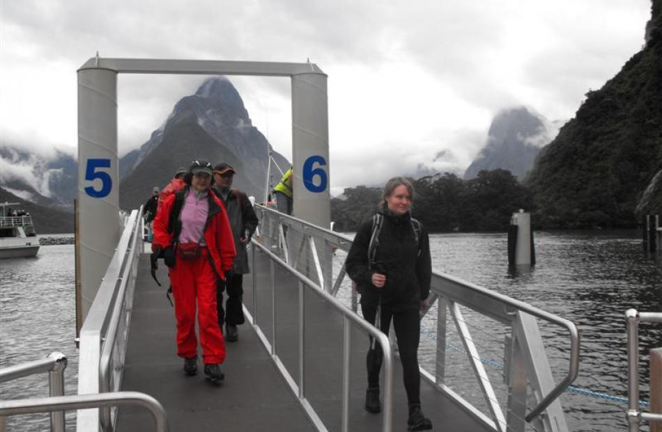 Milford Track trampers (left) arrive back safely at Milford Sound yesterday after experiencing...