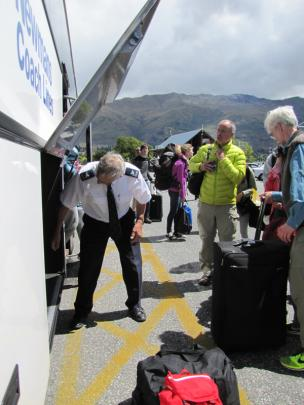 Newmans driver John Hamilton unloads bags at Wanaka after driving a full coach load of passengers...