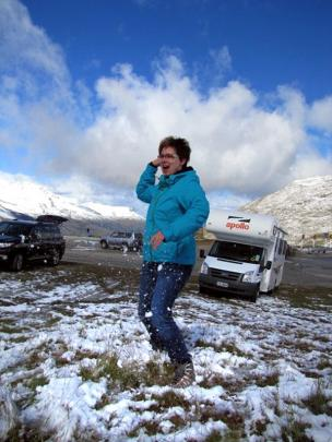 Katrin Einax, of Leipzig, Germany, dodges snowballs in the carpark at the top of the Crown Range,...