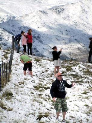 Tourists stop at the top of the Crown Range to play.