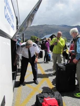 Newmans driver John Hamilton loads and unloads bags at Wanaka after driving a full bus of...