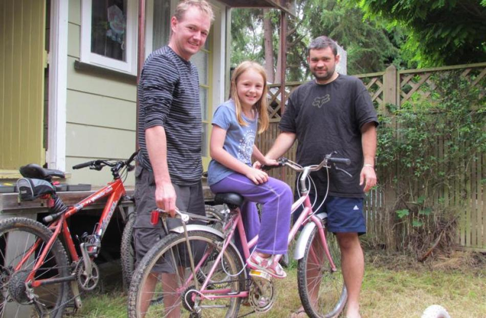 Bryce Saunders (left), Chelsea Saunders (8) and Aaron Hall prepare for a family bike ride at the...