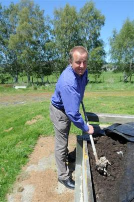 Dunedin International Airport assistant operations manager Steve Simpson rakes worm cast from a...