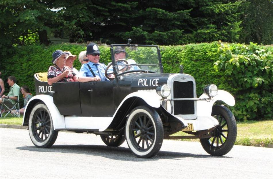 Leo O'Neill, of Mosgiel, drives the early 1920s police car from Naseby with John Levido (right),...