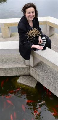 Garden manager Margo Reid feeds  fish at the Dunedin Chinese Garden. Photo by Peter McIntosh.
