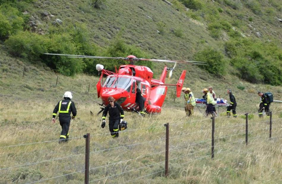 A seriously injured tourist is taken to the helicopter before being airlifted to Dunedin.