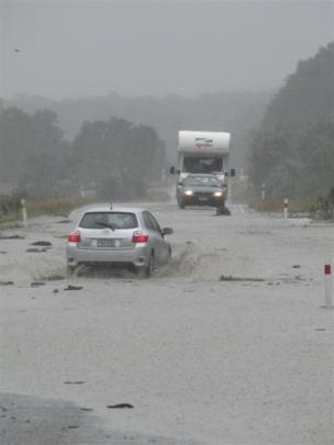 Motorists cautiously negotiate a flooded section of State Highway 6 about 2km north of Makarora...
