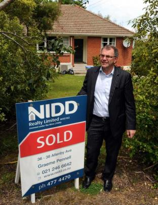 Property salesman Graeme Pennell stands outside a property he recently sold in the Dunedin suburb...