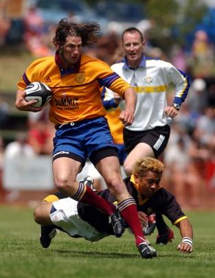 North Otago's Grant Johnston heads for the tryline in 2004 as Wellington's Joe Wright tries to...