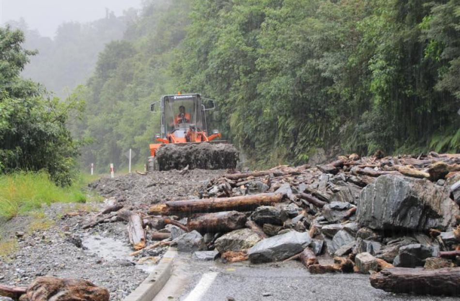 A loader starts work on a slip below the Gates of Haast bridge on State Highway 6 between Lake...