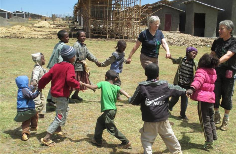 Volunteers Shona Somerville (far right)  and Liz Pyle  play with the village children. Photos by...