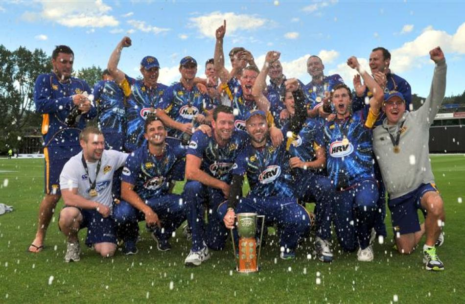 Bubbly flows as  Otago players and officials celebrate the team's four-wicket win over Wellington...