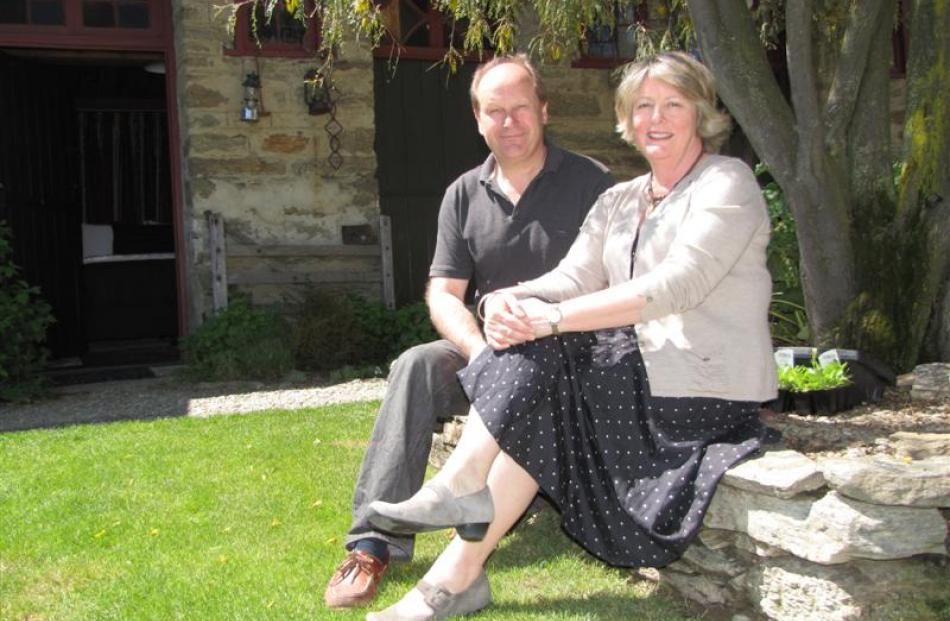 David and Andrea Ritchie sit among the restored buildings of Oliver's Lodge and Stables, formerly...