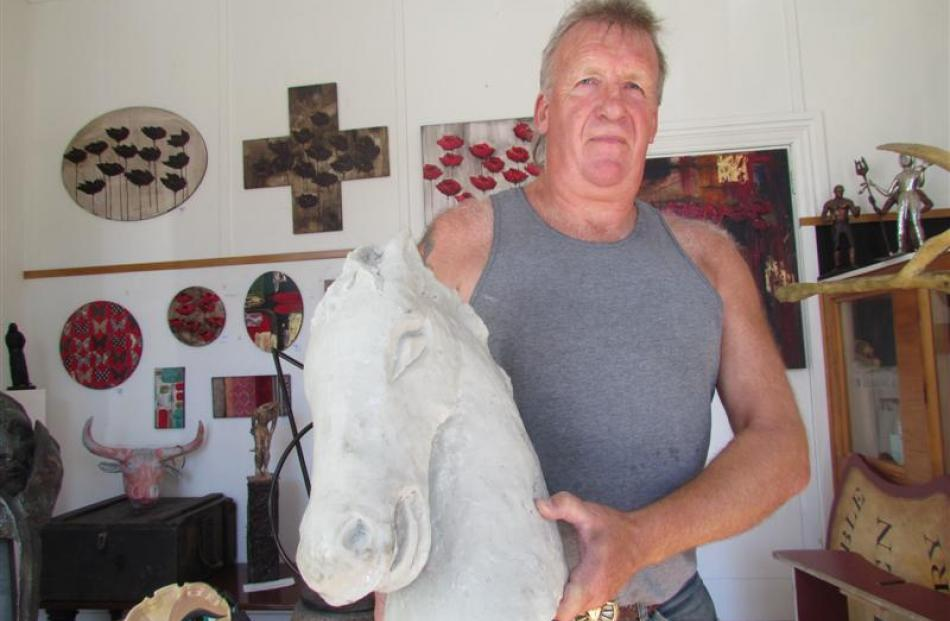 Sculptor Don Paterson with one of three horse heads to be installed on a carousel at the Friendly...