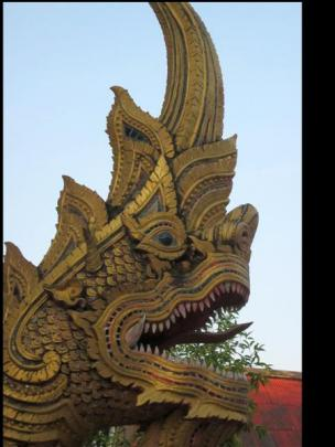 A fierce-looking creature gazes out from a Thai temple.