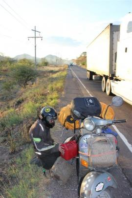 Tim Munro tops up his scooter's  petrol tank on the side of the highway leading to Honduran...