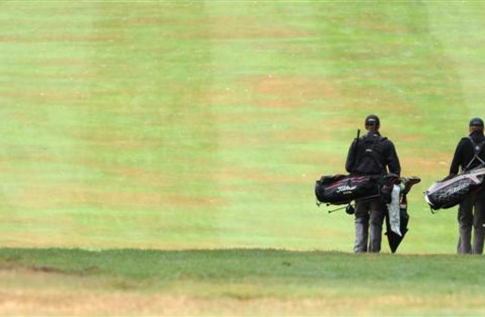 Golfers make their way up the fairway on the first hole.
