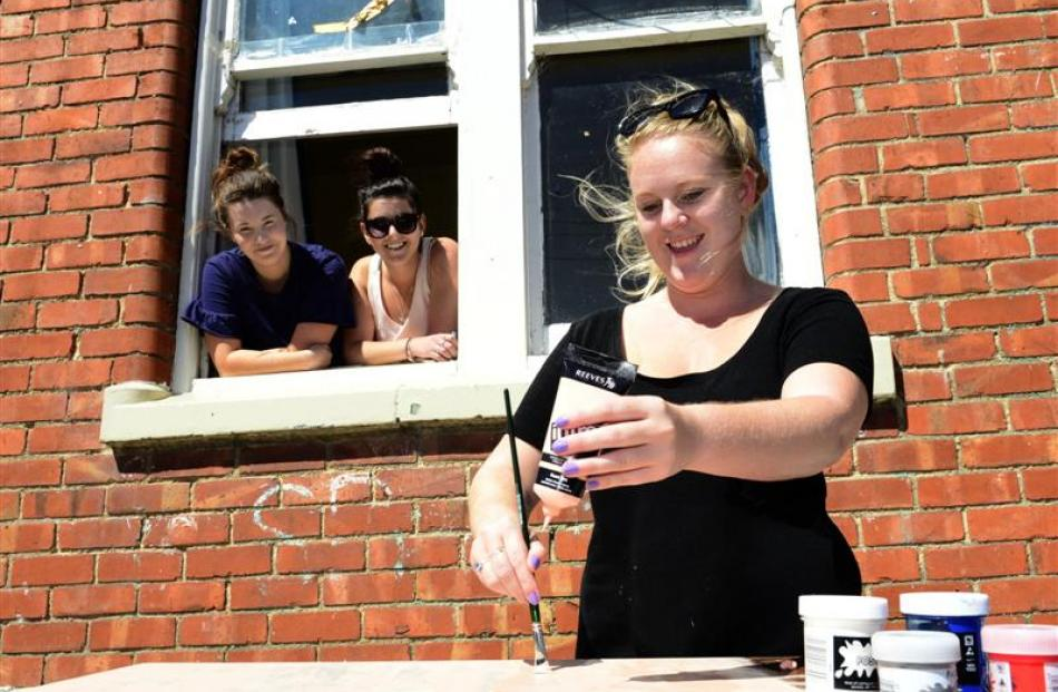 Becki Mudford (21), of Auckland, gives a table a fresh lick of paint, while (from left) Janelle...