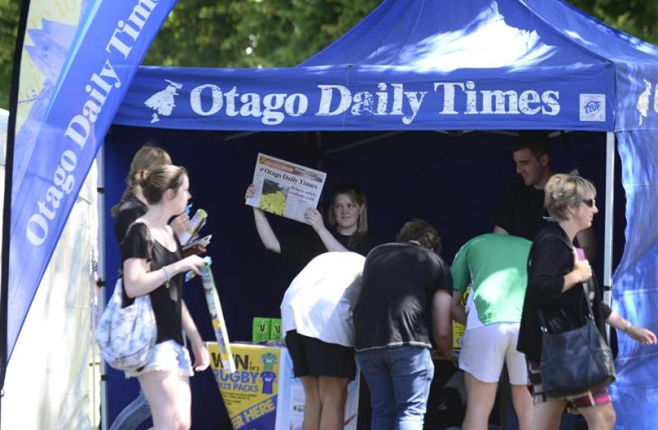 Jess Peck, of the Otago Daily Times, holds up a newspaper at one of the many stalls at tent city....