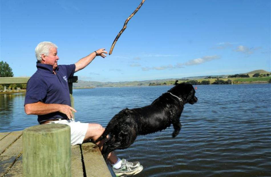 Lake Waihola Cafe & Bar owner Kevin Reid plays  with his dog Tess despite the warning signs about...