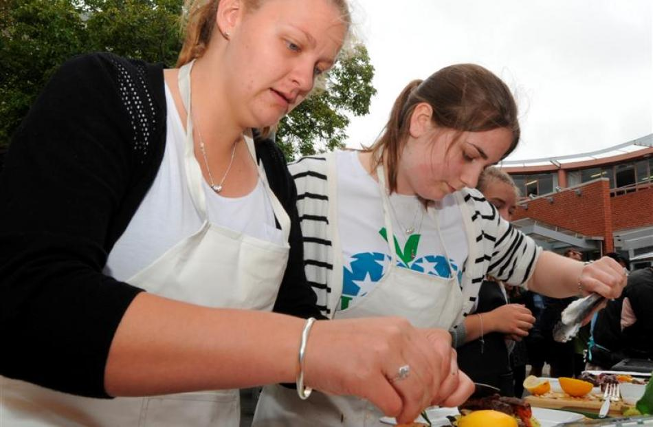 Preparing their dishes are Cecelia Hare (18, left) and Hannah Morton (19).