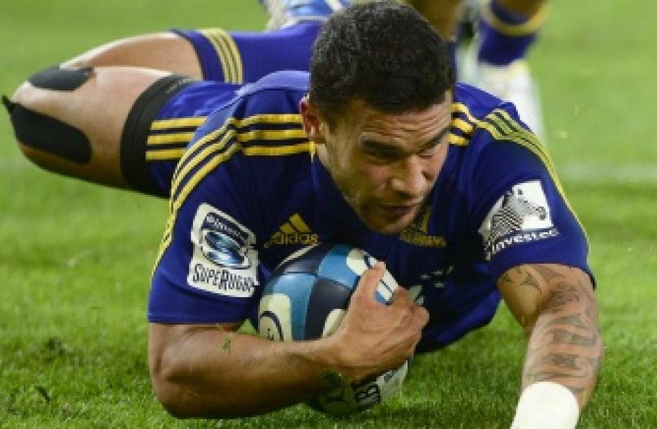 Highlanders winger Kade Poki skids over the line to score a try during his team's Super 15 match...