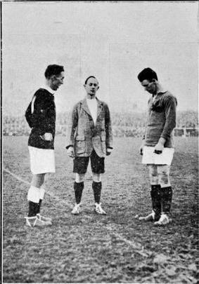New Zealand captain Dan Jones (left) and Canadian captain Jack ''Red'' Monaghan wait for referee...