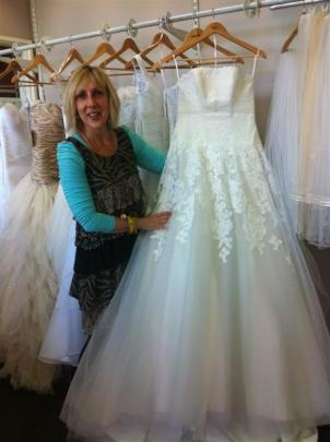 Staff member of Je T'aime Bridal Boutique, Lana Marston, with a gorgeous gown
