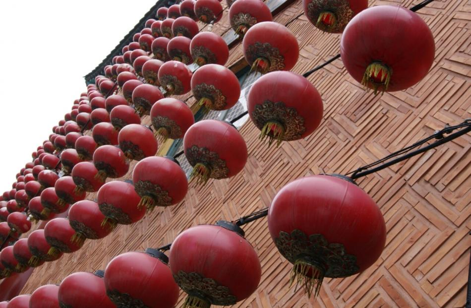 Bright red lanterns cover a side of a building in Chinatown.