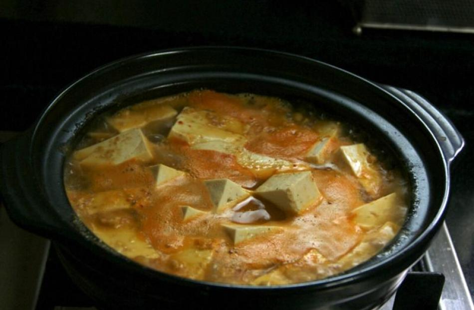 Tofu soup bubbling away on the stove.