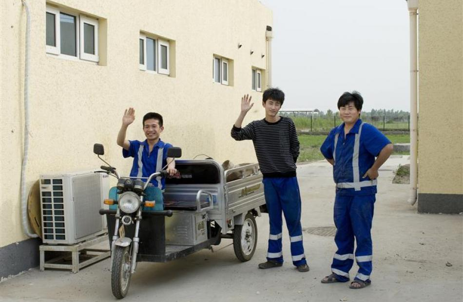 Workers on Fonterra's Yutian 2 dairy farm pose for the camera.